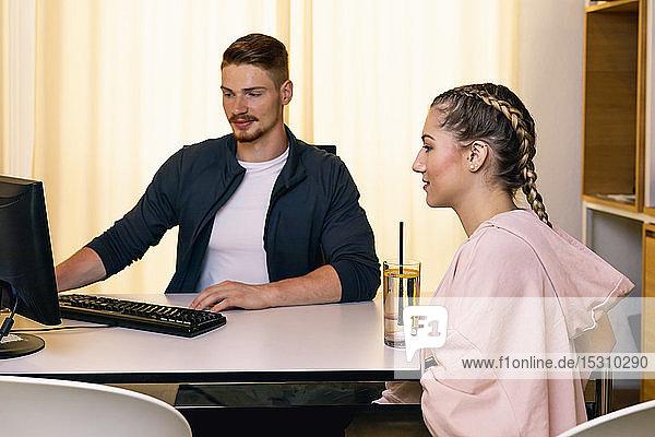 Junge Frau im Gespräch mit einem Angestellten am Schreibtisch in einem Fitnessstudio