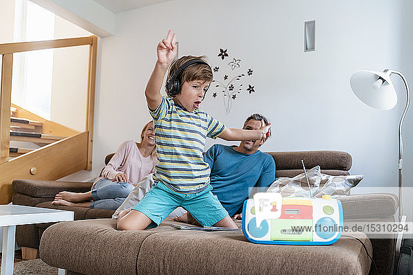 Excited boy listening to music with headphones on couch at home with parents in background