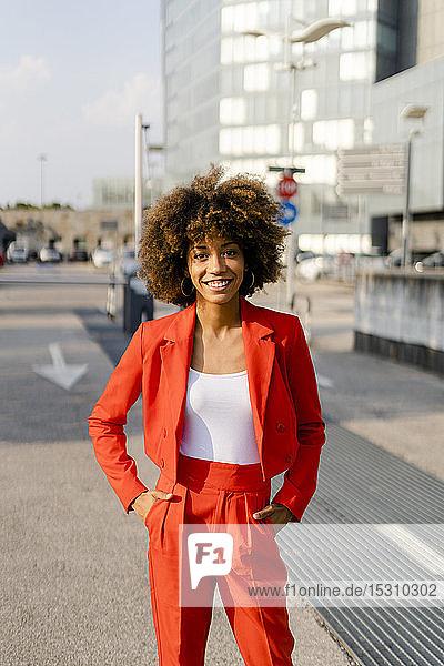 Porträt einer lächelnden jungen Frau in einem modischen roten Hosenanzug