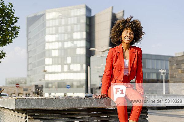 Porträt einer lächelnden jungen Frau in einem modischen roten Hosenanzug in der Stadt