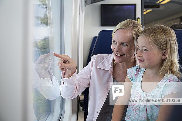 Mutter und Tochter reisen mit dem Zug und zeigen aus dem Fenster