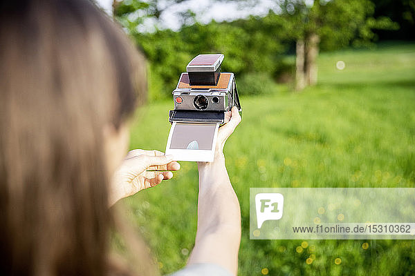 Close-up of woman taking instant photo on a meadow