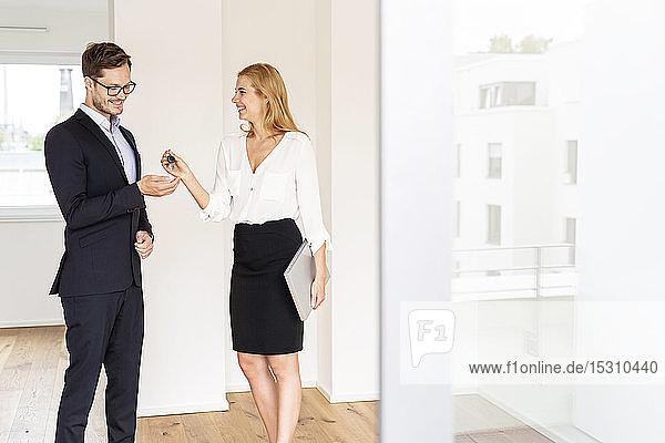 Immobilienmakler übergibt Schlüssel an Kunden im neuen Haus