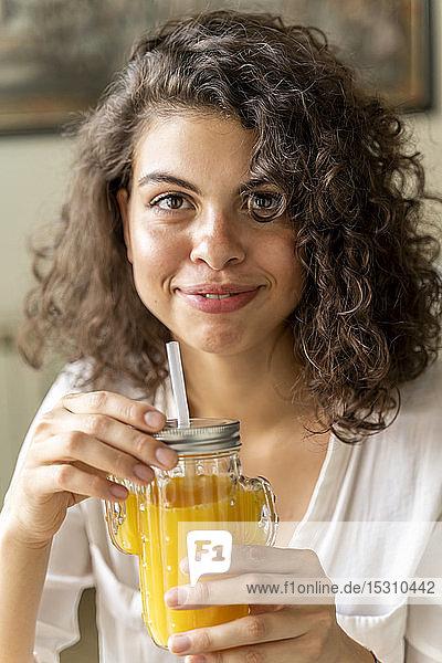 Porträt einer lächelnden jungen Frau mit einem Glas Orangensaft