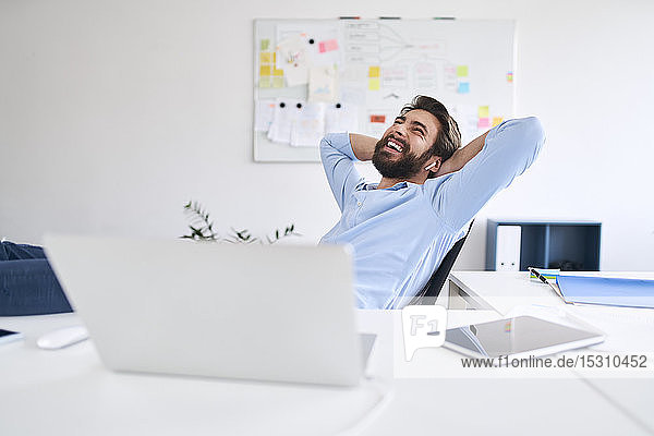 Laughing businessman sitting at a desk