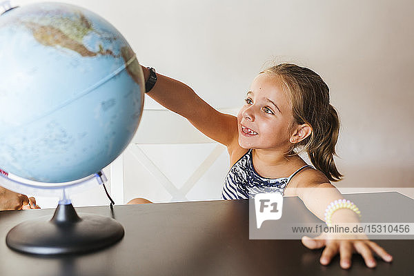 Happy schoolgirl looking at globe on desk