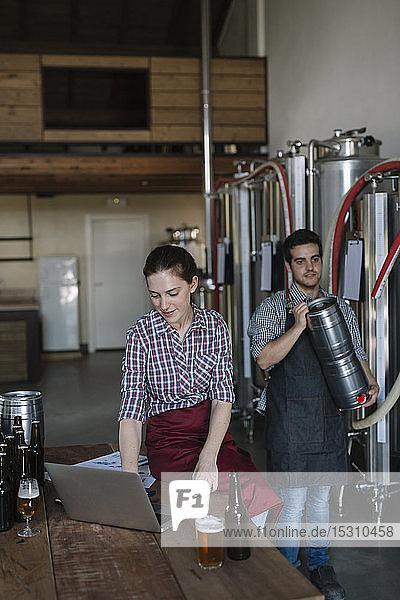 Junge Unternehmer arbeiten mit Laptop in einer Brauerei
