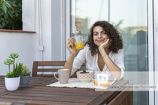 Portrait of smiling young woman with orange juice on balcony