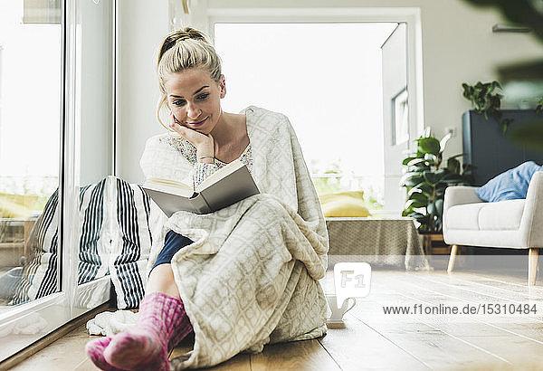 In eine Decke gehüllte Frau sitzt zu Hause am Fenster und liest ein Buch