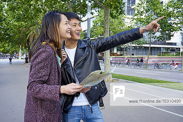 Tourist couple visiting the city and holding a map  Barcelona  Spain