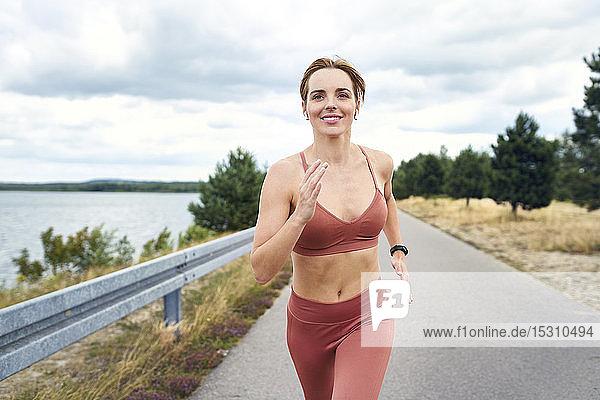 Porträt einer lächelnden athletischen Frau  die im Freien joggt