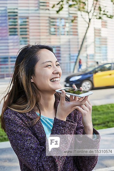 Happy woman sending a voice message with cell phone  Barcelona  Spain