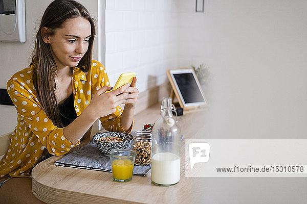 Junge Frau benutzt Mobiltelefon und frühstückt zu Hause in der Küche