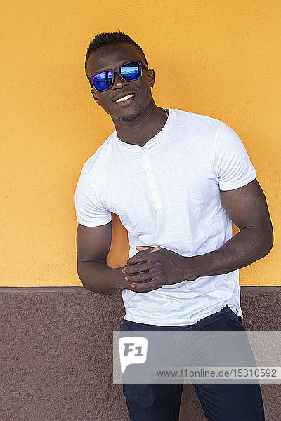 Portrait of smiling young man wearing white t-shirt and sunglasses