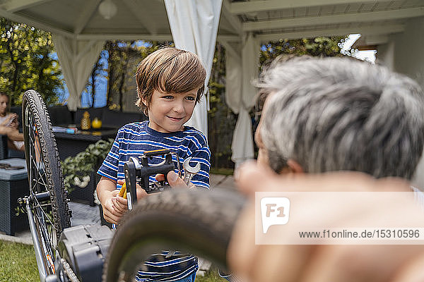 Father and son repairing a bicycle in garden