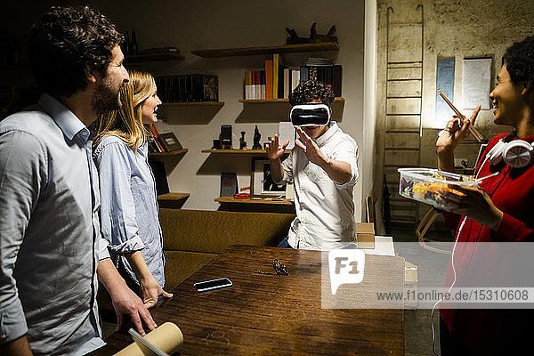 Kollegen sehen Mann mit VR-Brille im Büro an