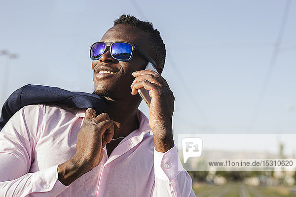 Young businessman with sunglasses using his smartphone outside