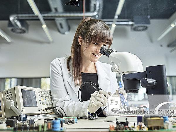Löttechnikerin unter dem Mikroskop