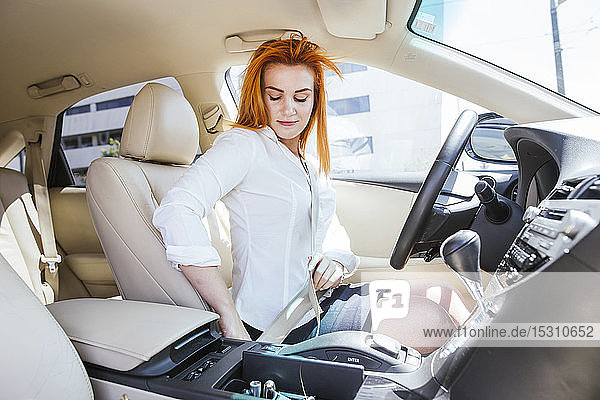 Business woman in a car fastening her seat belt