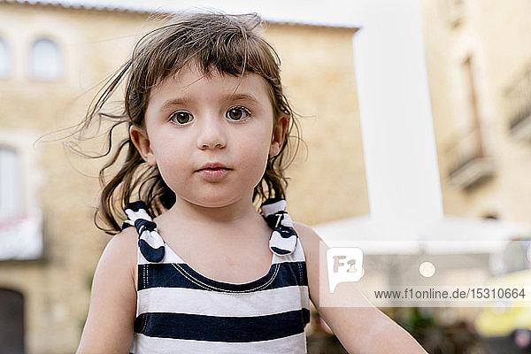 Bildnis eines süßen kleinen Mädchens im Sommer in einem gestreiften Kleid