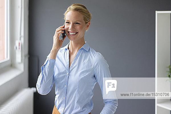 Lächelnde junge Geschäftsfrau telefoniert im Büro per Handy