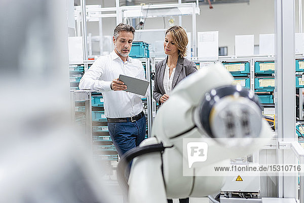 Businesswoman and man with tablet talking at assembly robot in a factory