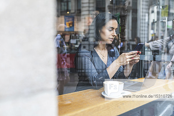 Business woman having a break in a cafe and working with laptop and smartphone