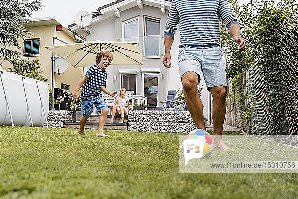Father and son playing football in garden