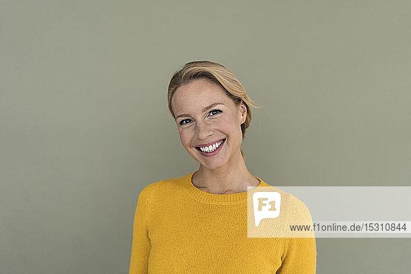 Porträt einer lächelnden blonden Frau  die einen gelben Pullover trägt