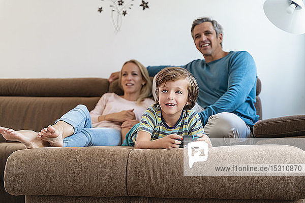 Boy lying on couch at home playing video game with parents watching