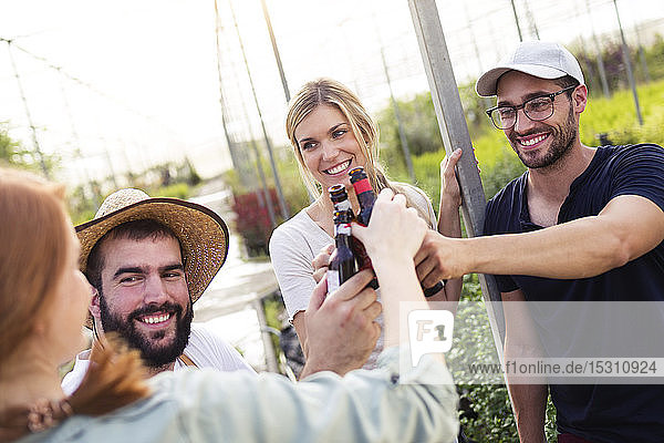 Group of friends toasting with bottles of beer in the greenhouse