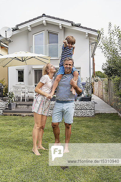 Portrait of father with wife carrying son on shoulders in garden