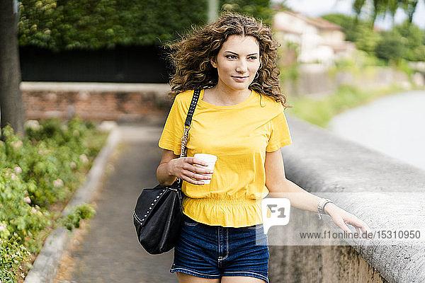 Junge Frau geht in der Stadt mit Einwegbecher