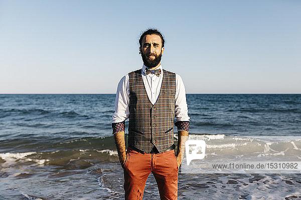 Porträt eines gut gekleideten Mannes  der an einem Strand am Wasser steht