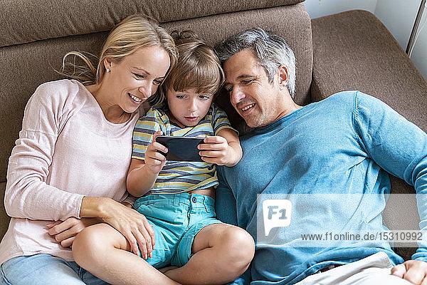 Vater  Mutter und Sohn telefonieren zu Hause auf der Couch