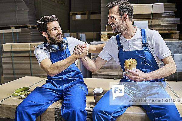 Zwei glückliche Arbeiter machen Mittagspause in der Fabrik