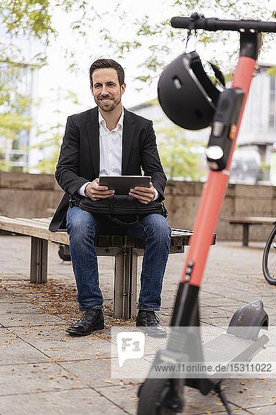 Geschäftsmann mit E-Scooter mit Tablet in der Stadt