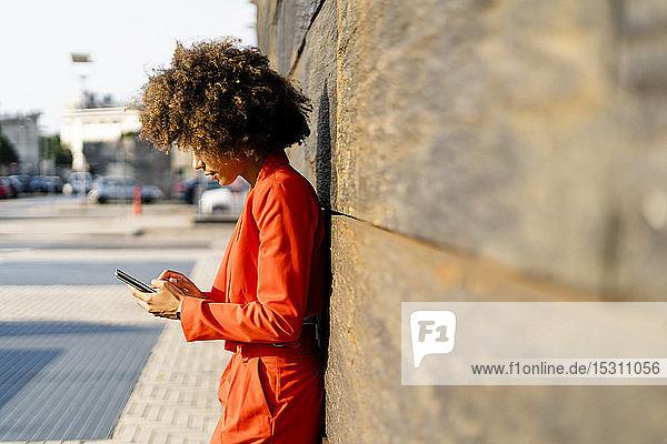Junge Frau in modischem roten Hosenanzug lehnt mit Handy an Wand
