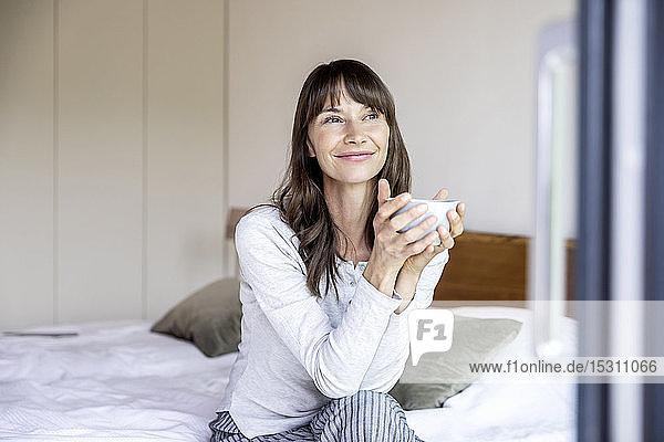 Entspannte Frau mit Tasse Kaffee sitzt zu Hause auf dem Bett