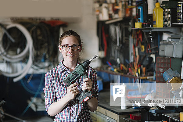Porträt einer selbstbewussten  frauenhaltenden Übung in ihrer Werkstatt
