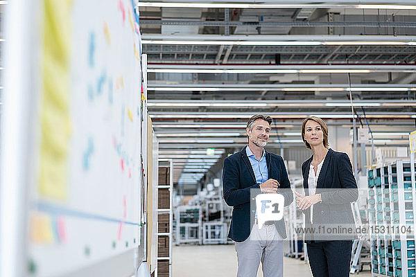 Geschäftsmann und Geschäftsfrau im Gespräch in einer Fabrikhalle