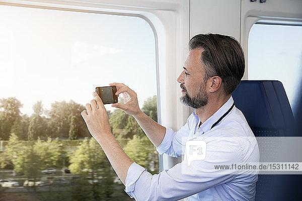 Älterer Mann sitzt in einem Zug und fotografiert mit seinem Smartphone