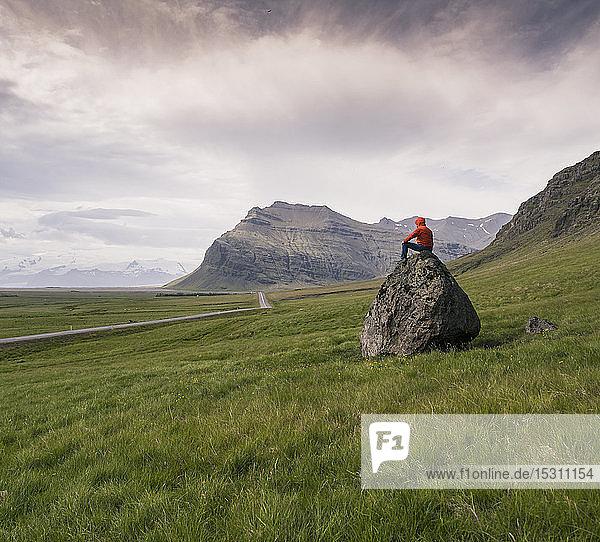 Auf einem Felsen sitzender Mann in der südlichen Region  Island