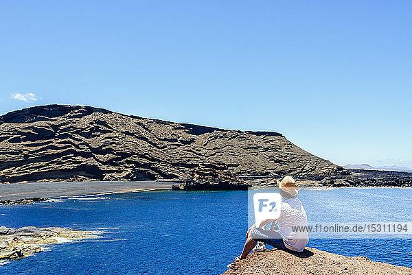 Man sitting on cliff looking towards El Golfo beach  Lanzarote  Canary Islands  Spain