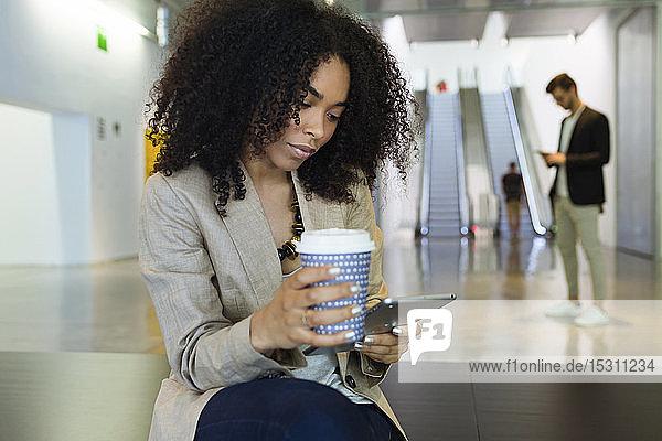 Junge Geschäftsfrau mit Kaffee zum Mitnehmen und Smartphone in einem Foyer