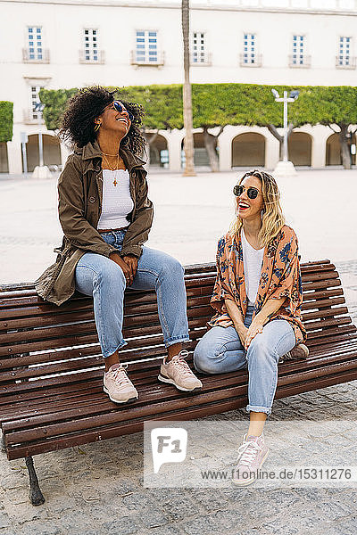 Multikulturell glückliche Frauen auf der Bank sitzend