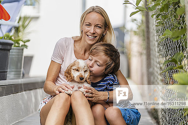 Portrait of mother snd son cuddling with cute dog puppy