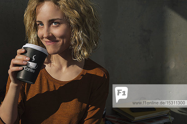 Portrait of smiling young woman drinking coffee to go at home