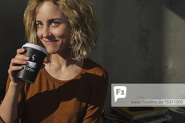 Porträt einer lächelnden jungen Frau  die Kaffee trinkt  um nach Hause zu gehen