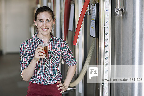 Portrait of confident young woman holding beer glass at a brewery
